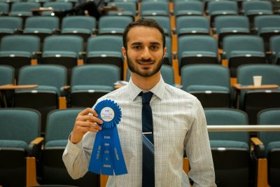 Man standing in front of empty auditorium seats holding award ribbon