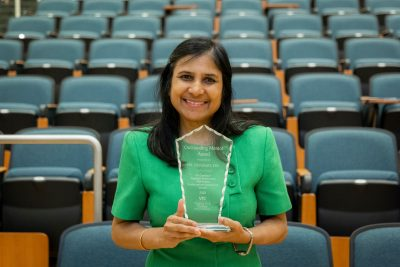 Dr. Devasmita Dev holding trophy for research mentor of the year 2020