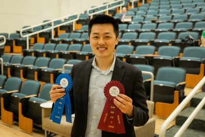 Tom Liu holding two award ribbons: letter of distinction for scholarship and productivity