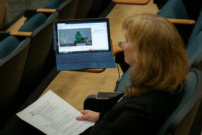 View from above of woman sitting in auditorium with laptop to the side and holding notes