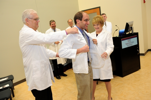 Dean Cynda Ann Johnson and Dr. Daniel Harrington present student Alex Weller with his white coat.
