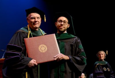 Andrew Hanna recieves his diploma from Interim Dean Dan Harrington.