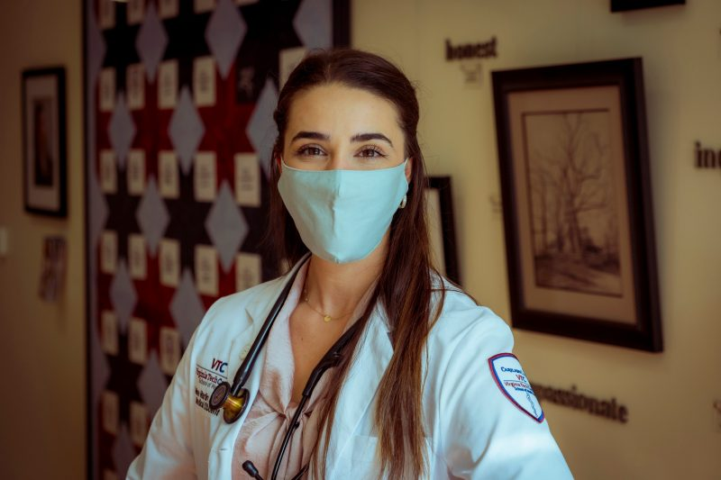 Female medical student with white coat and stethescope stands in front of a colorful wall.