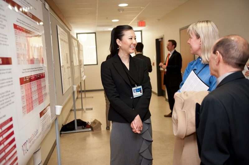 Virginia Tech Carilion School of Medicine student Alice Chen discusses her research project with Research Day participants.