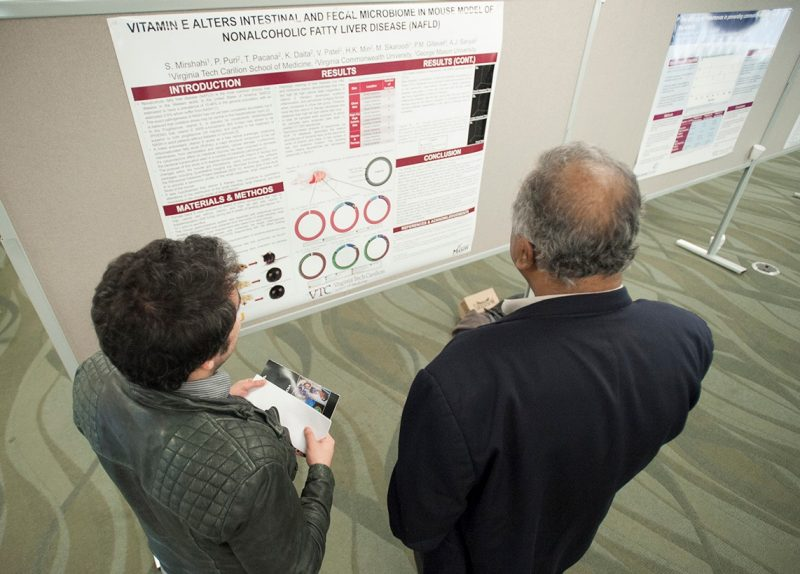 student Shervin Mirshahi examines his research project poster with his advisor, Dr. Puneet Puri.
