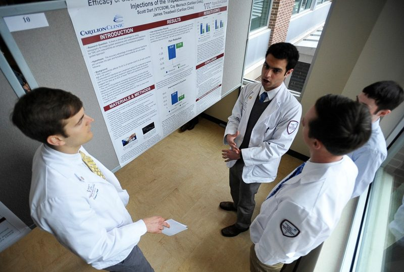 Four medical students discuss a poster presentation.
