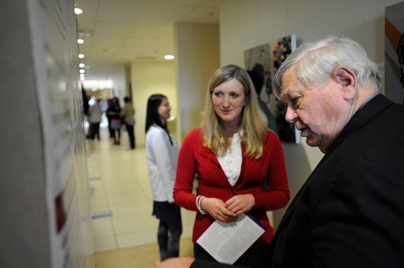 Carlie Blake, a member of the Class of 2015, and Dr. Harry Dorn, an assistant professor at the Virginia Tech Carilion Research Institute, study her poster presentation.