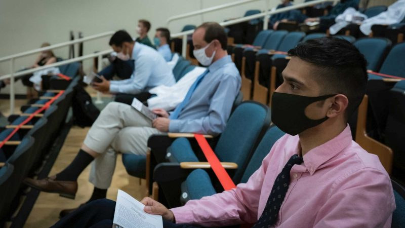close up of a row of masked students, physically spaced, in the auditorium. Red tape marks where seats are not available.