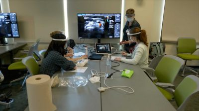 Four students, each wearing masks and faceshields, are seated around a table, looking at a large screen with an ultrasound image