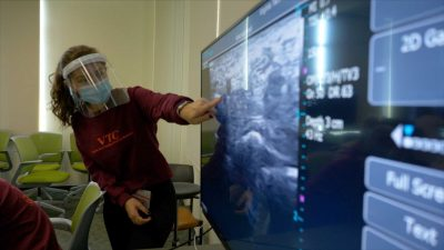 A student, wearing a mask and face shield, points at an ultrasound image on a large screen