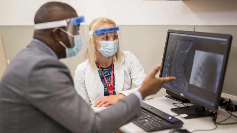 Physicians reviewing X-rays on a monitor