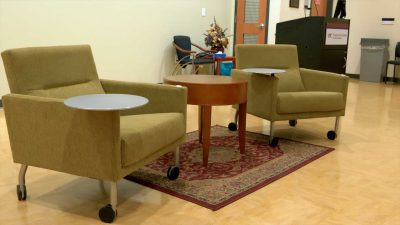 A small seating area at the front of the room, with two lounge chairs and a round table.