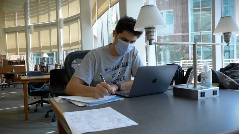 A student, wearing a mask, is taking notes while viewing his laptop.