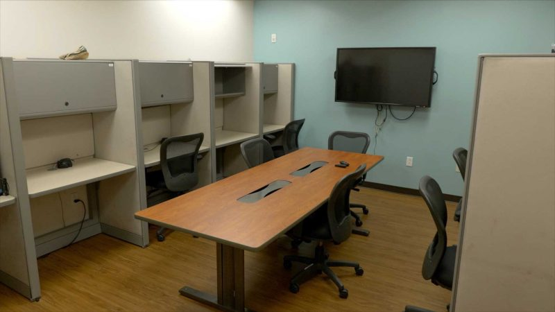 An empty PBL Team Room featuring small cubicles, a large screen on the wall, and a table in the center of the room.