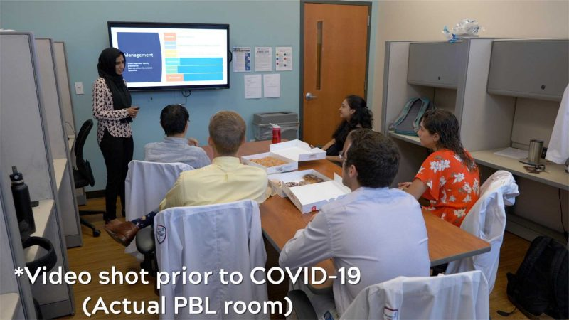 One student presenting at the large screen and five students sit around the table. Image was taken prior to COVID.