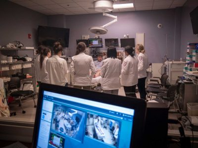 Foreground a screen with footage from two cameras. In the background we see seven medical students talking to a standardized patient in a simulated exam room.