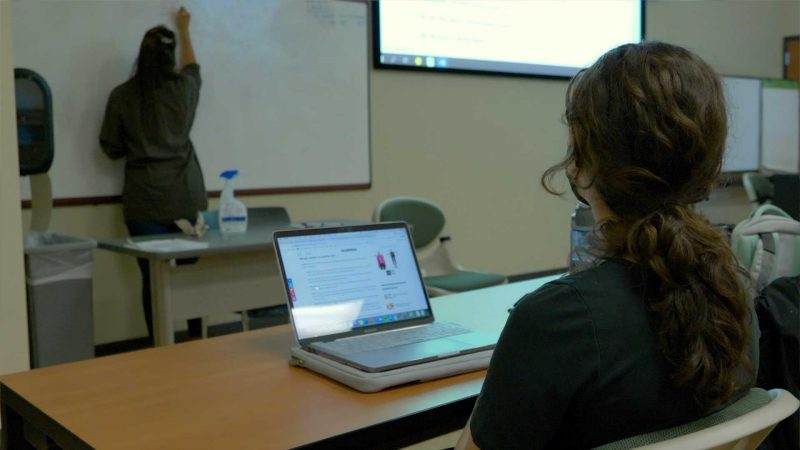 The back of a student, who is looking at a faculty member at the white board.
