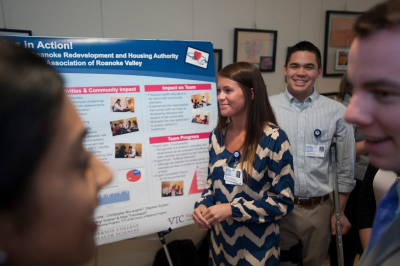 Students discuss their service learning project during the poster presentation day.