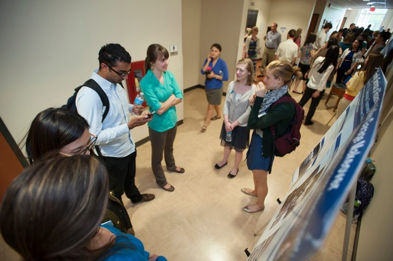 Students and visitors browse the service learning project posters.