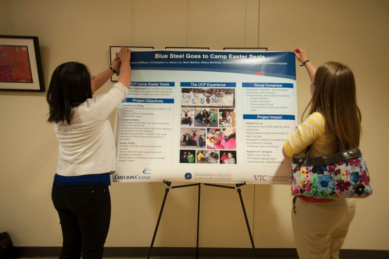 Students setting up their poster for the Service Learning Poster day.