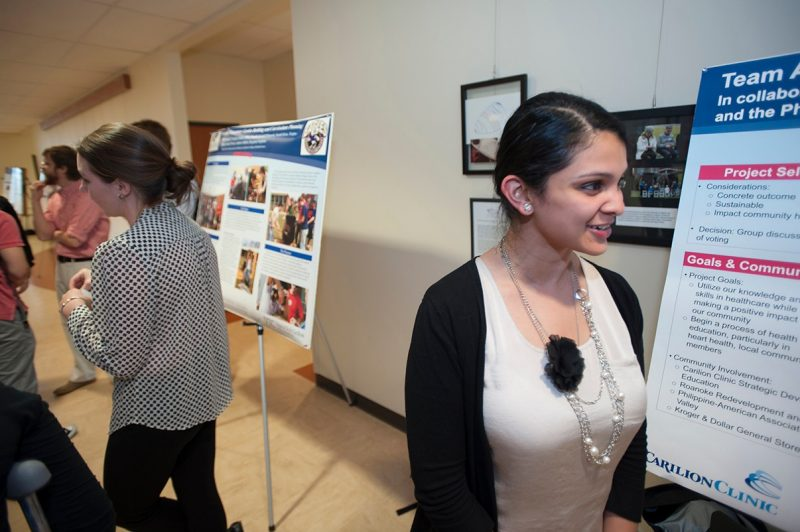 A Virginia Tech Carilion School of Medicine first-year student examines another project at the Service Learning Poster Day.