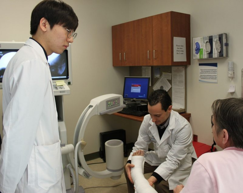 Student JongWook Oh observes as Dr. Franco Coniglione re-casts patient Frances Huffman's ankle.