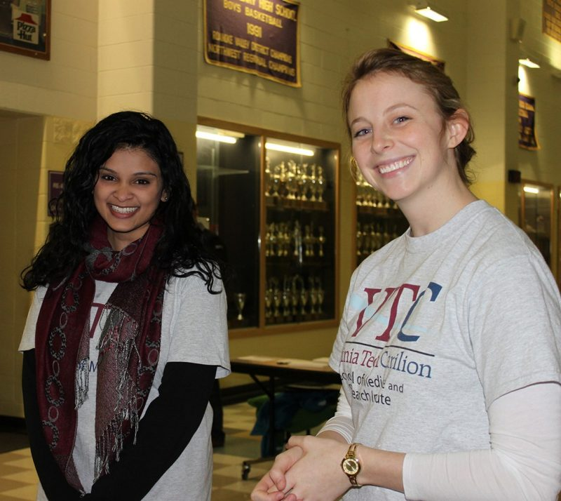 Tarangi Sutaria, '17, and Caroline Reist, '18, greet guests near the donation table.