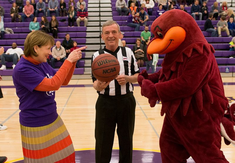 Carilion Clinic CEO Nancy Agee faces off against the Hokie Bird at tip-off.