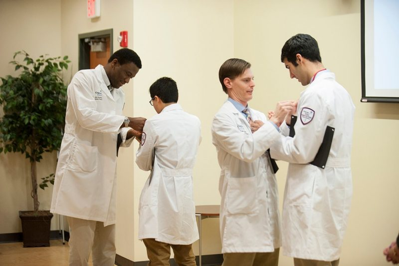 Resident inductees place pins on each other as part of their admittance into the Gold Humanism Honor Society.