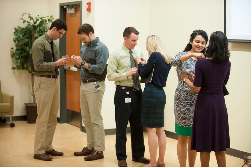 Medical students place pins on each other after being inducted into the Gold Humanism Honor Society.
