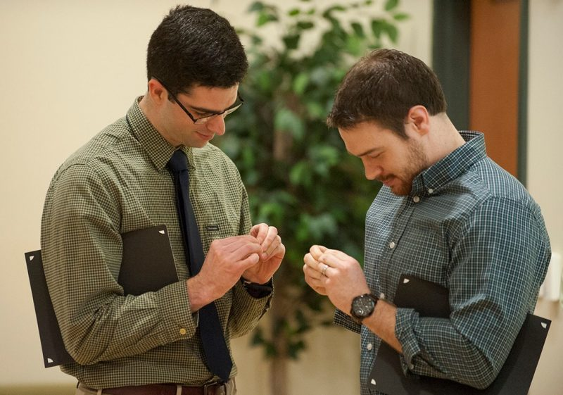 Michael Gallager (left) and Nathan Johnson work to open pins they received as part of the Gold Humanism Honor Society induction ceremony.