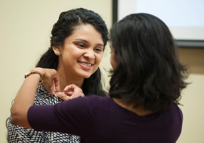 Tarangi Sutaria (left) has a pin placed on her by Silpa Thaivalappil as part of the induction ceremony into the Gold Humanism Honor Society.