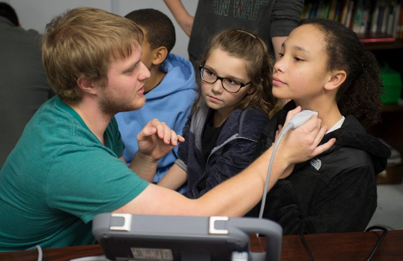Class of 2019 student Spencer Lovegrove demonstrates a portable ultrasound to two young girls by holding the ultrasound to one of the girls' neck