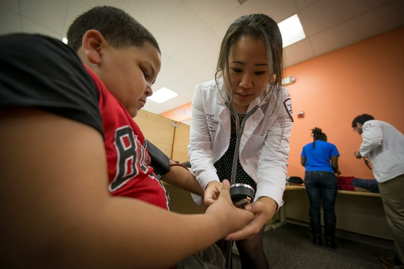 Judy Chen demonstrates how to take a blood pressure reading on a member of the Boys and Girls Club.