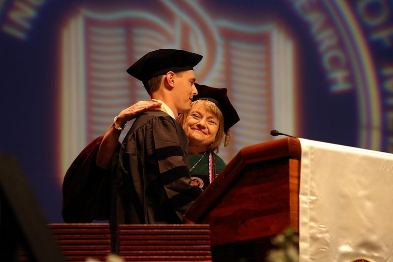 Dean Cynda Johnson congratulates class president Matthew Joy