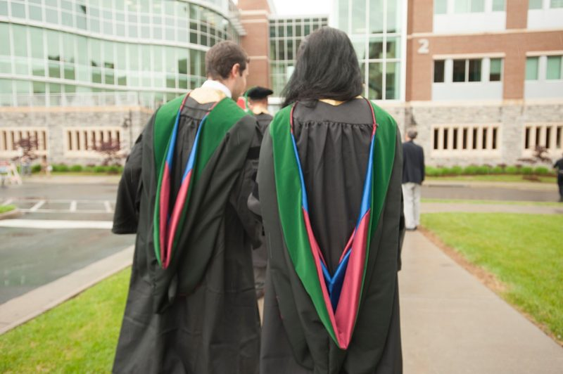 Two students walking away from the camera towards the School of Medicine, wearing the custom designed hoods