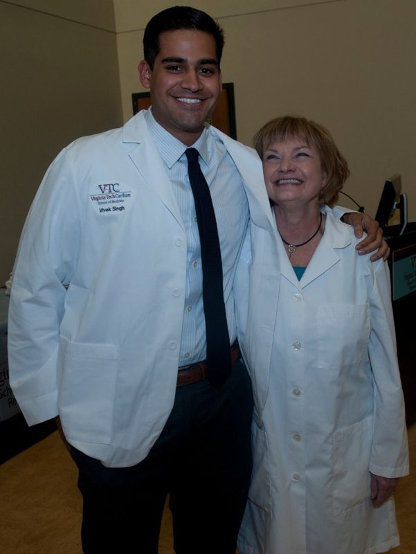 Vivek Singh poses with Dean Cynda Johnson, MD, after receiving his white coat.