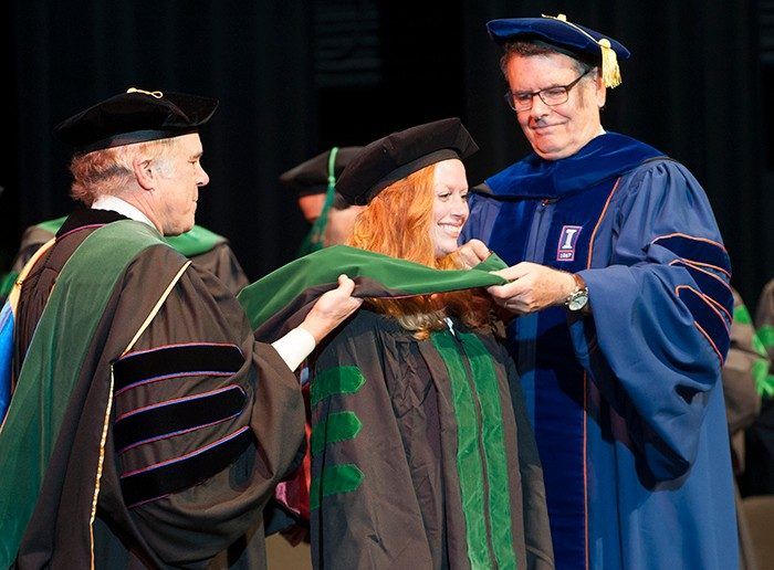 Megan Whitham is hooded by Dr. Bruce Johnson and Dr. Michael Friedlander