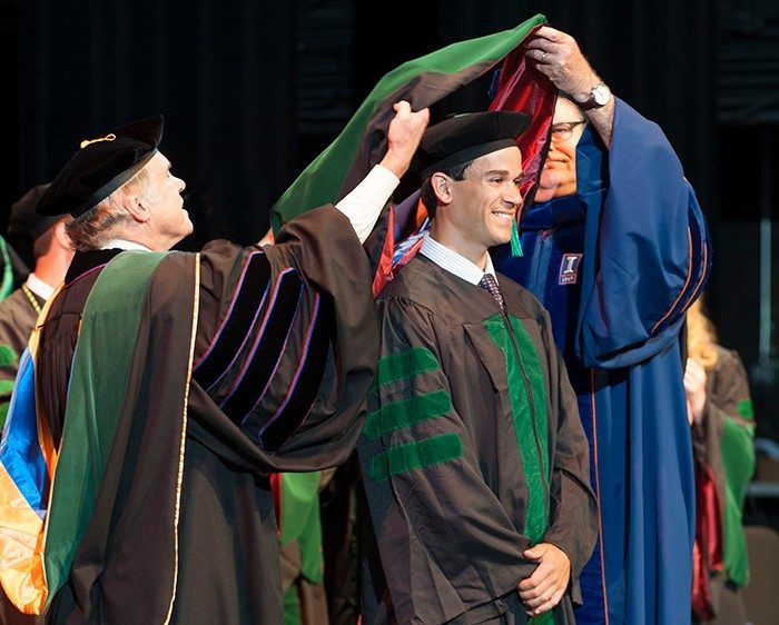 Robert Varipapa is hooded by Dr. Bruce Johnson and Dr. Michael Friedlander