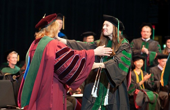 Graduate Lauren Poindexter is overjoyed to receive her diploma from Dean Cynda Johnson.