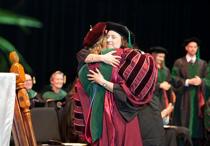 Lauren Poindexter embraces Dean Cynda Johnson as she receives her diploma.