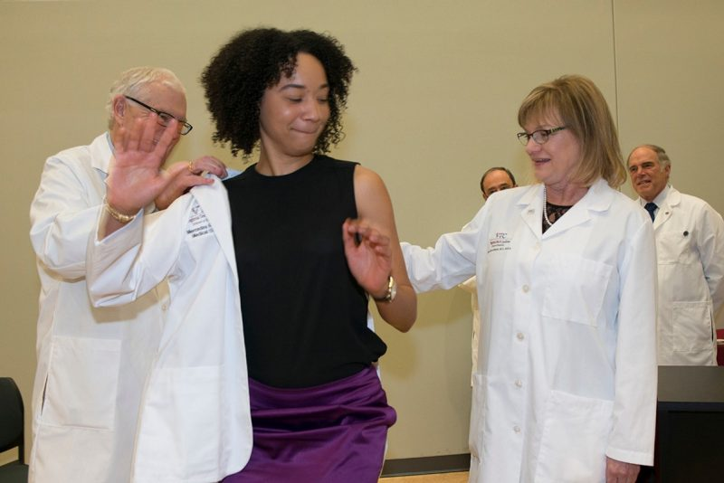 Mercedes Robinson (center) receives her white coat from Dean Cynda Johnson and Vice-Dean Dan Harrington during the Class of 2019's White Coat Ceremony at the Virginia Tech Carilion School of Medicine.