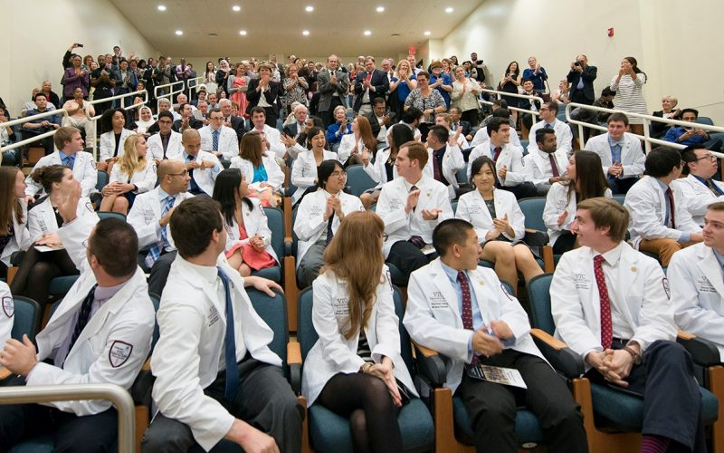 Members of the Virginia Tech Carilion School of Medicine's Class of 2019 look back at family and friends after receiving their white coats.