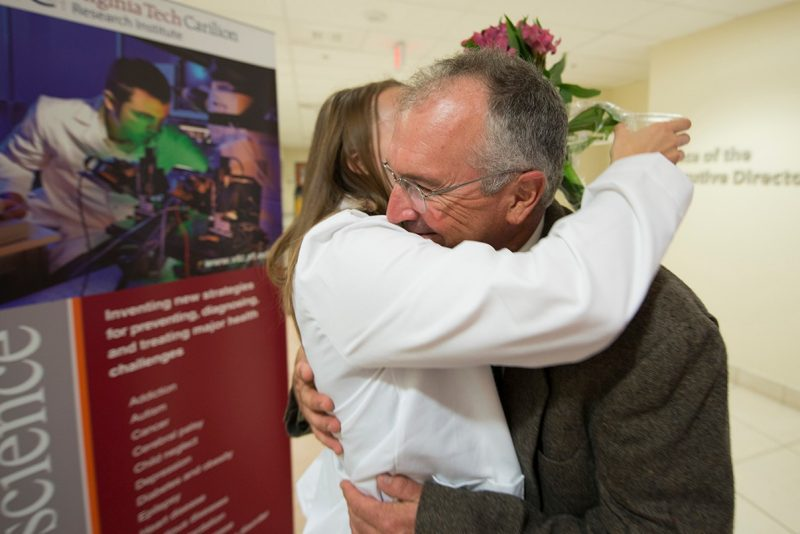 Becky Gates of the Virginia Tech Carilion School of Medicine's Class of 2019 receives a hug during a reception after the school's white coat ceremony.
