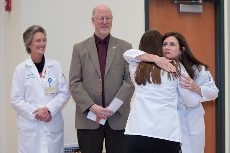 "A member of the Virginia Tech Carilion School of Medicine's Class of 2019 receives a hug from Tarin Schmidt-Dalton, M.D as David Musick, PhD and Tracey Criss, MD look on during the school's annual ""White Coat Ceremony""."