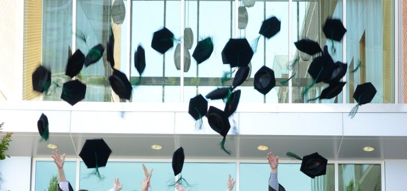 Members of the class of 2016 toss their tams in the air after graduation exercises of the Virginia Tech Carilion School of Medicine.
