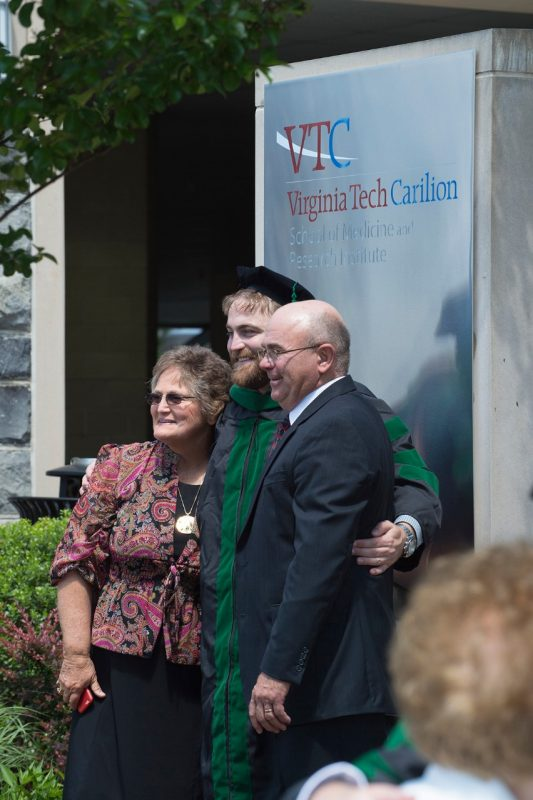 Dr. Daniel Fish stands with his parents in front of the sign at the Virginia Tech Carilion School of Medicine after graduation exercises for the Class of 2016.