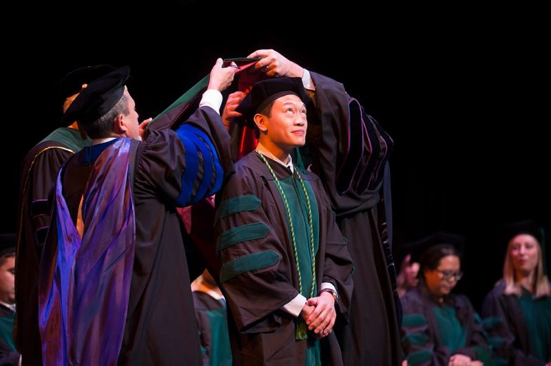 Francis Bustos, M.D. looks up as faculty members place his hood on his shoulders.