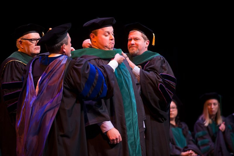 Matthew Addis, M.D. receives his ceremonial hood as part of graduating.