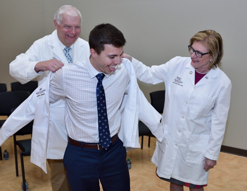 Andrew Brown helped into his white coat